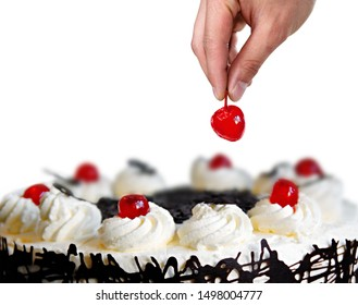 Hand placing the cherry on the cake with white background.
