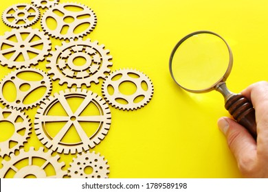 hand placing a magnifying glass over set of gears mechanism