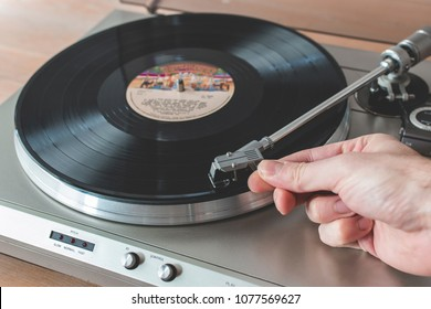 Hand placing the needle of a record player onto a spinning vinyl record