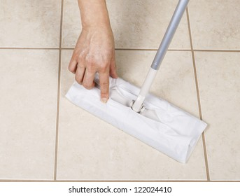 Hand placing paper wiper on cleaning broom for bathroom tile sweep