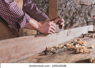 Hand plane being used by off camera carpenter wearing plaid shirt to smooth long wooden plank