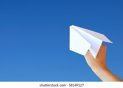 Hand with a plane on the sky background