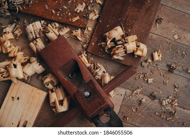 A hand planer and wood shavings on the tile floor