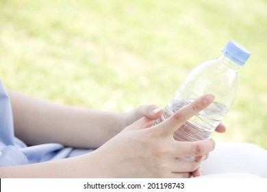 The hand with a plastic bottle