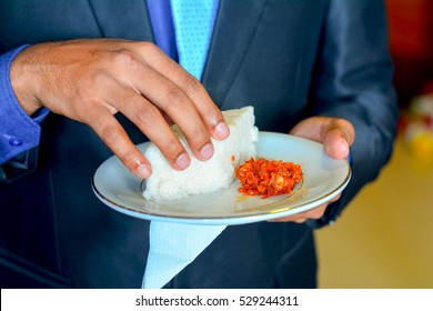 Hand and plate with Kiribath or Milk rice.  Kiribath is a traditional Sri Lankan food made from rice and coconut milk which is used to be a main food on any cultural ceremony or occasion