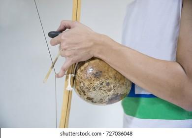 hand playing berimbau on white background