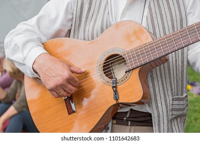 An hand playing a guitar.