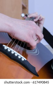 hand playing on an acoustic guitar