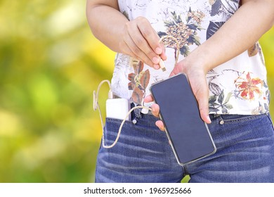 Hand was plugged into the power bank cable, connected to the mobile phone to charge, not running out of power. Idea for mobile power backup according to the way of relying on mobile phones in life.