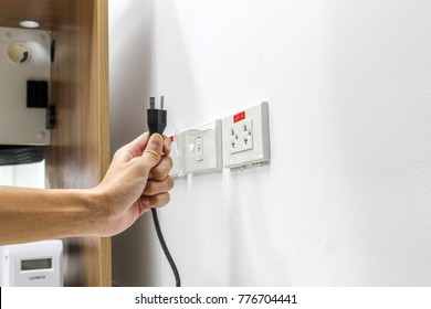 Hand are plugged in or unplugged electricity. Separated from a white background.