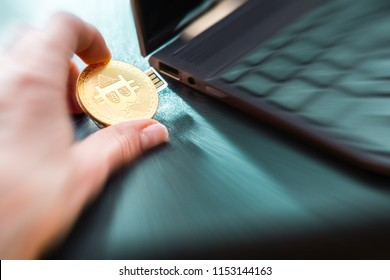 A hand plugging in a Bitcoin thumb drive into windows laptop