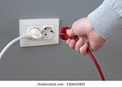 Hand plugging in an electric cord into a white plastic socket or  european wall outlet on grey plaster wall. Closeup of a woman's hand inserting an electrical plug into a wall socket. Daylight.