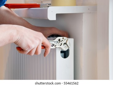 hand of a plumber with wrench and radiator