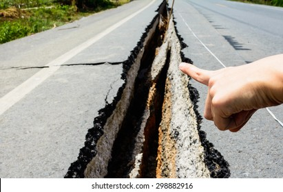 hand point to cracked road, cracked road aftetr earthquake