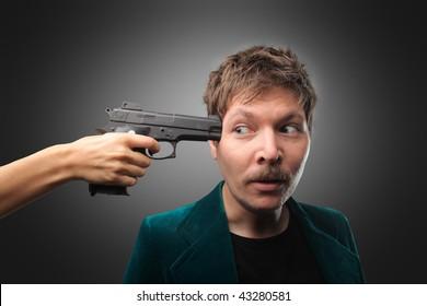 hand pointing gun against man's head
