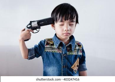 hand pointing gun at the head boy