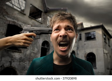 hand pointing gun at the head of man