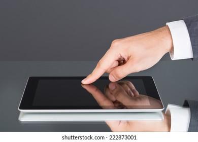 Hand pointing at tablet computer screen. Closeup shot