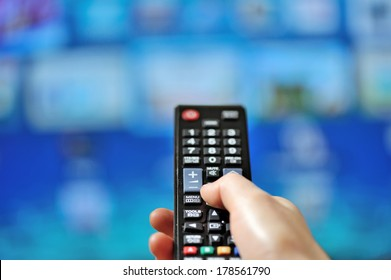 Hand pointing tv remote control and tv set