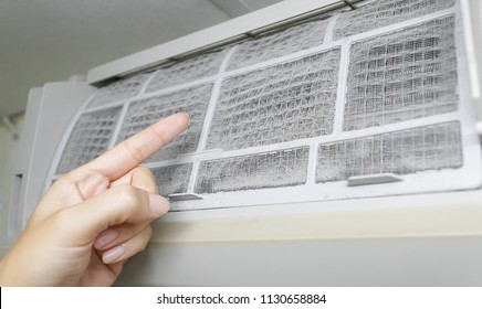 Hand pointing at a very dirty air-conditioner filter that needs cleaning