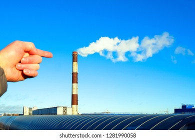 The hand points to the smoke from the pipe. Industrial part of the city. Industrial zone. Pipe smoke pollutes the atmosphere. pipeline over the road