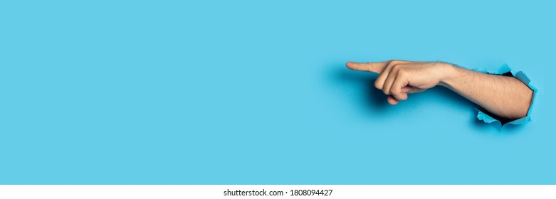 Hand points to something on a blue background. Gesture look at this, pay attention