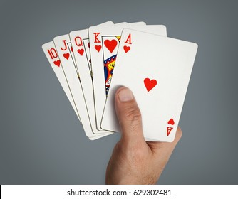 Hand with poker cards, grey background.