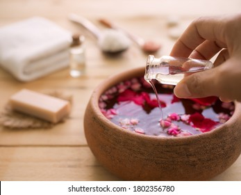 Hand pour coconut oil in to aroma smell rose with blur image of soap, towel, massage oil, salt spa on wood background.  Aroma therapy spa set for luxury hotel or professional massage salons concept. - Shutterstock ID 1802356780