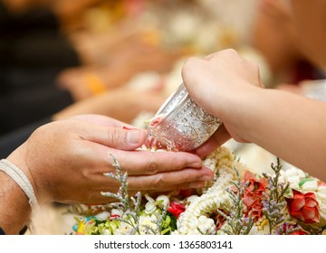 Hand  pour water and flowers on the hands peple old  and happy for the songkran festival. concept gives blessing in Songkran day Thailand