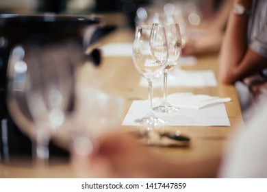 Hand is pouring a bottle of light dry wine into glasses for tasting during the celebration. The concept of exclusive wines from wineries. Wine tasting on a trip
