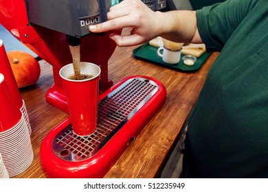 hand pouring cola in red cup. stylish soda machine on wooden desk. take to go. catering in food court at mall concept. space for text. modern kitchen