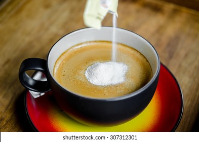 Hand pouring creamer in to a cup of coffee on wooden background.