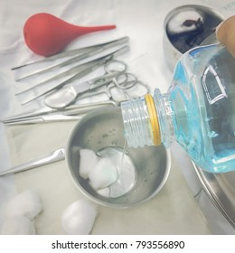Hand is pouring the disinfectant bottle into the surgical device and wounding the patient.