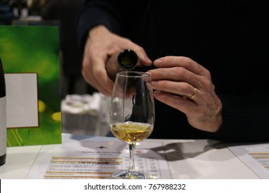 "Hand pouring French white wine called ""coteaux du layon"" in to a glass. French wine fair ""vigneron independant winemaker"""