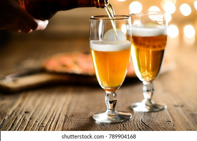 hand pouring fresh beer on a glass with pizza on wood restaurant table indoor with cosy dim light