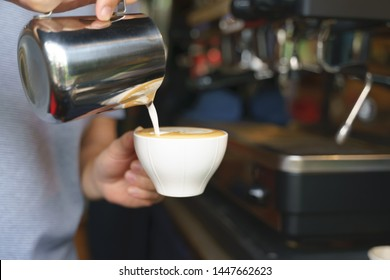 Hand pouring frothy steamed milk into coffee for making latte hot drink