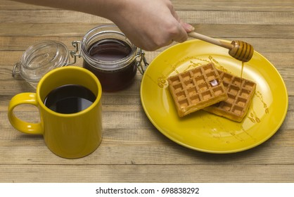 hand pouring honey Viennese waffles on yellow plate