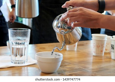 Hand pouring hot water over roasted or ground coffee bean cup for aroma smell testing, professional barista training for coffee shop & restaurant concept. Drip brewing & filtered pour-over method