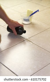 Hand pouring hydrogen peroxide on bathroom floor tile grout. Putting hydrogen peroxide on floor grout with baking soda, scrub brush and scrub sponge in back.