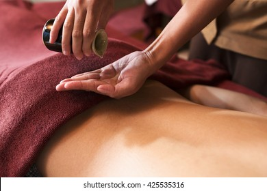 Hand pouring oil for massage in spa