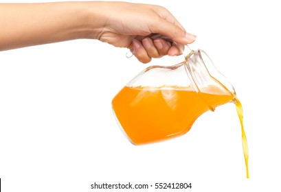 Hand pouring orange juice from jug isolated on white background