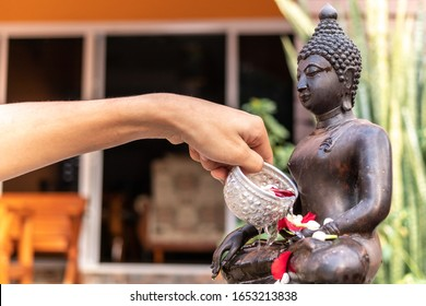 Hand pouring water to buddha statue. Buddha statue water ceremony in songkran festival, thailand.