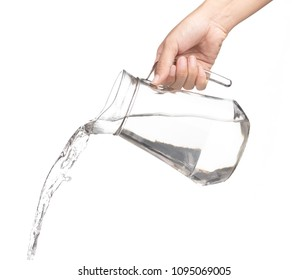 Hand pouring water from glass jug to glass isolated on a white background