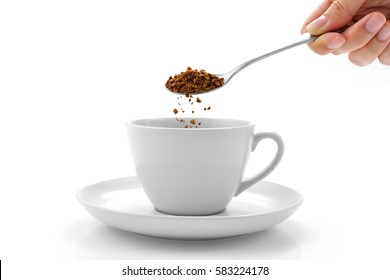 Hand pours instant coffee from a spoon in a coffee cup