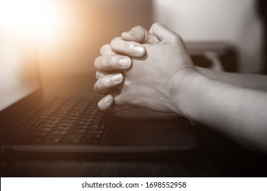 Hand praying with laptop, Church online Sunday services concept, Home church during quarantine coronavirus Covid-19, Hands folded in prayer concept for faith.