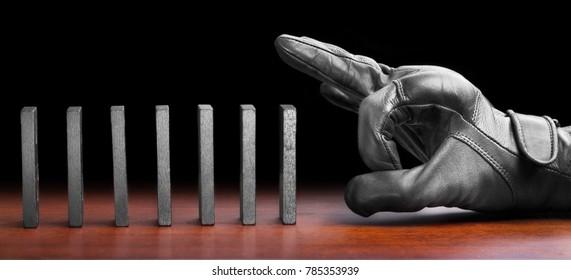 Hand prepared to push domino pieces to symbolize domino effect