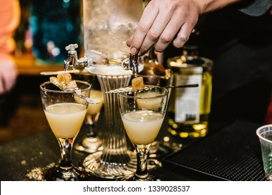 Hand preparing cocktails made from absinthe at an event