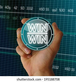 a hand presents digital round button with a win win icon on it in front of a electronic data table from stock market