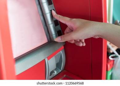 Hand press bottom on ATM bank machine to withdraw money