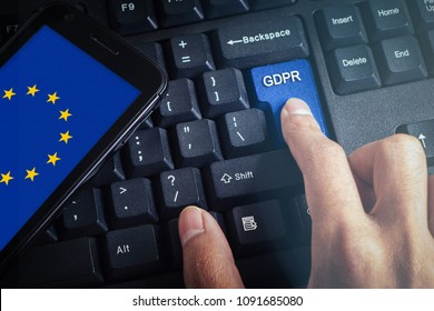 Hand press the button GDPR on keyboard with smartphone